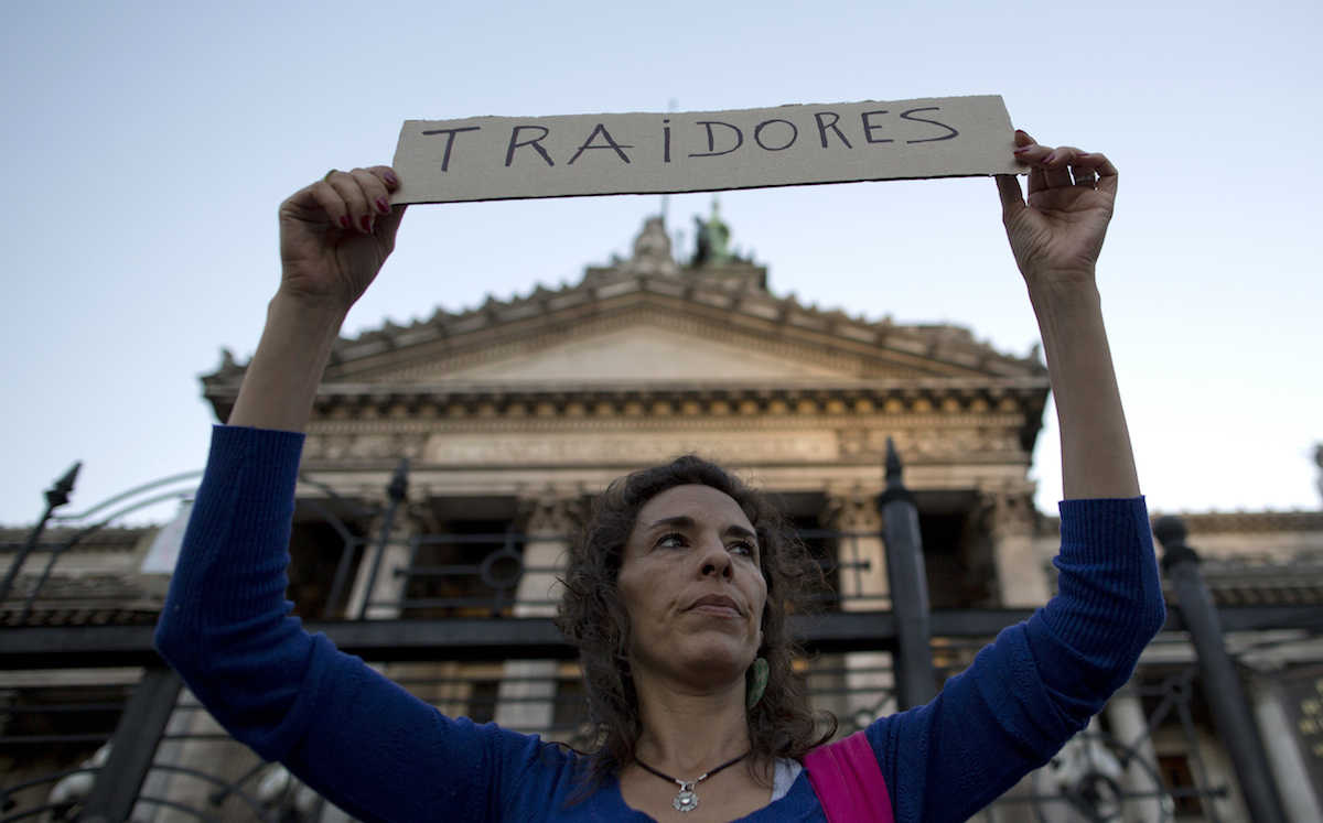 "A demonstrator holds a sign that says in Spanish: ""Traitors"" outside Congress, directed at lawmakers who are debating a new debt payment deal with U.S. creditors in Buenos Aires, Argentina, Wednesday, March 30, 2016. Under the deal, if passed, Argentina would pay to resolve all related claims, including those from a group led by hedge fund manager Paul Singer's group in New York. (AP Photo/Natacha Pisarenko)"