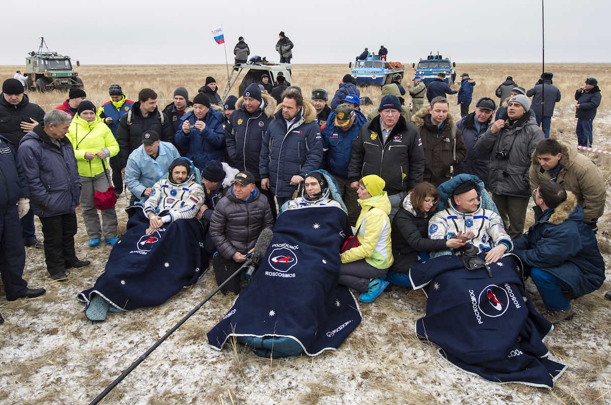 Russian cosmonauts Mikhail Kornienko, left, Sergey Volkov, center, and U.S. astronaut Scott Kelly rest in chairs outside the Soyuz TMA-18M space capsule after they landed in a remote area outside the town of Dzhezkazgan, Kazakhstan, on Wednesday, March 2, 2016. Kelly and Kornienko are completing an International Space Station record year-long mission to collect valuable data on the effect of long duration weightlessness on the human body that will be used to formulate a human mission to Mars. Volkov is returning after six months on the station.  (Bill Ingalls/NASA via AP)